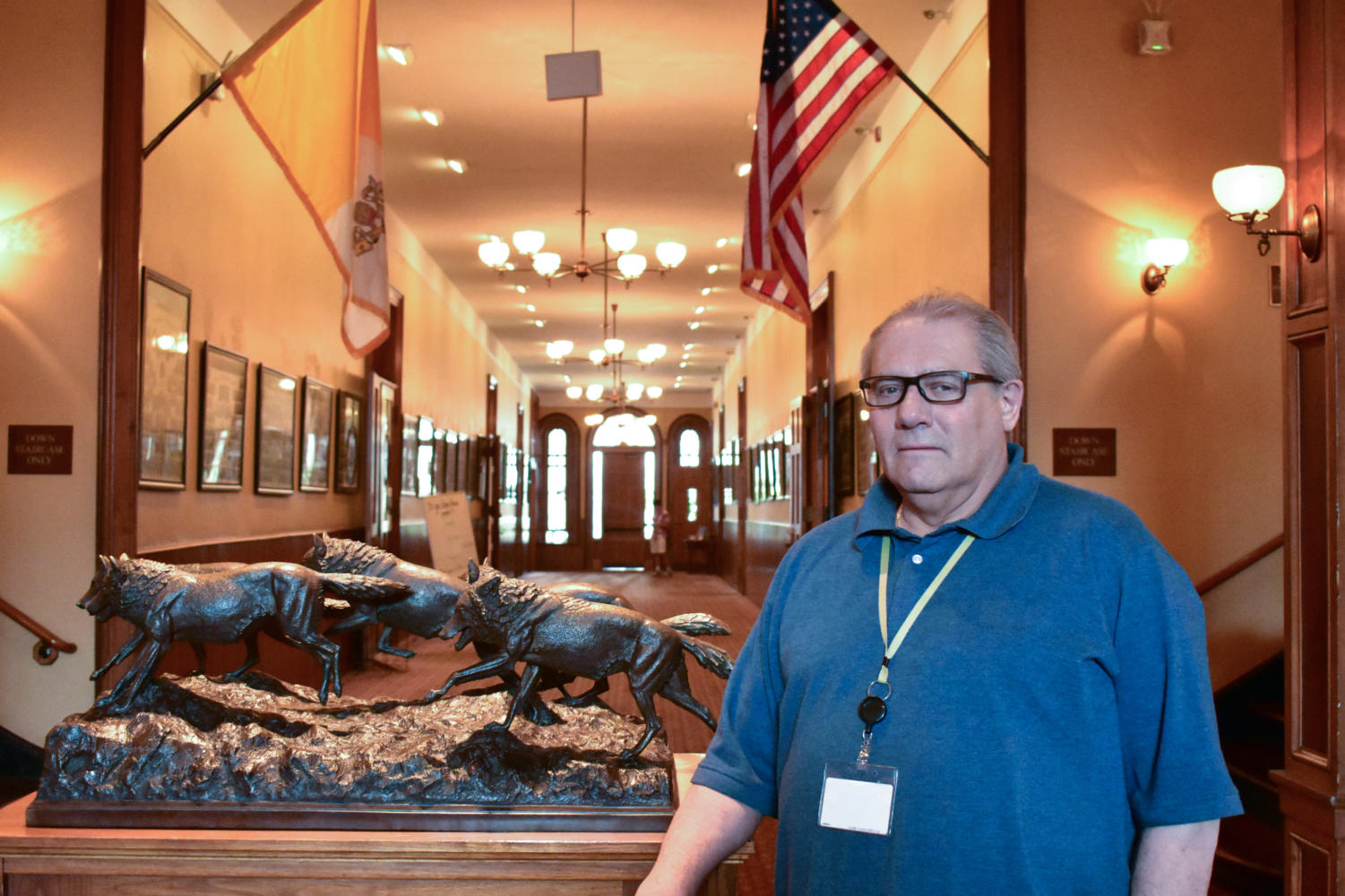 Mr. Luzzi stands by the wolf statue outside his office. Courtesy of Dan Solis '19.