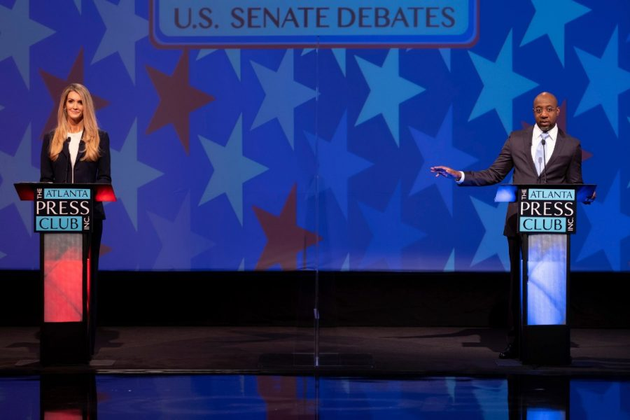 Kelly Loeffler(R) and Rev. Raphael Warnock(D) on the debate stage as the election approaches
